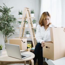 young woman opening cardboard box and looking upset with plants behind her
