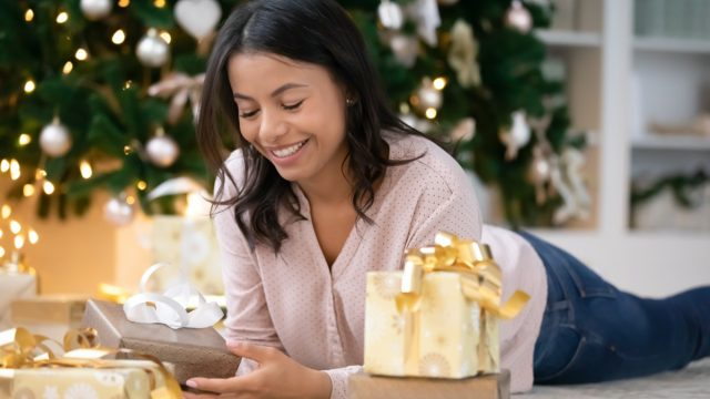 young woman opening present while lying on the floor