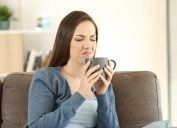 young woman making upset or disgusted face while looking at her gray teacup