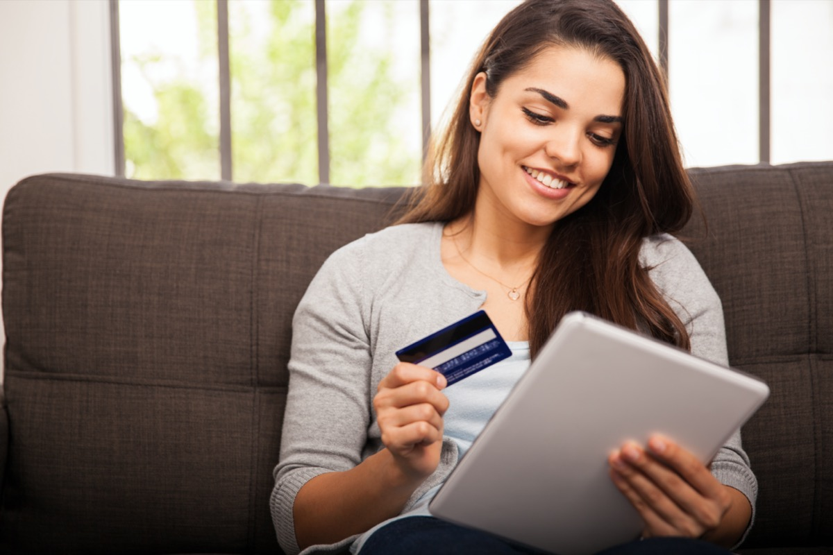 young woman smiling while holding tablet and credit card