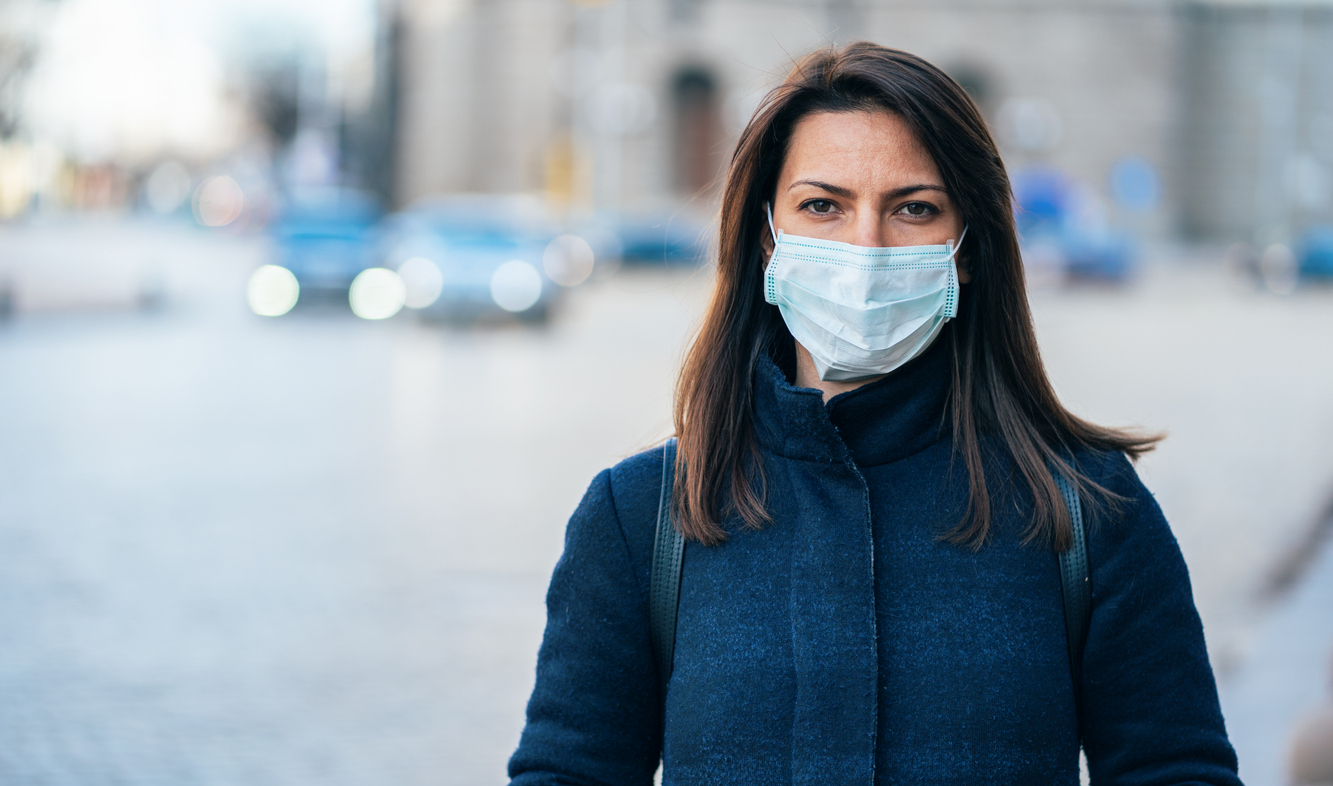 A woman wearing a warm jacket and a face mask while standing outside in a city.