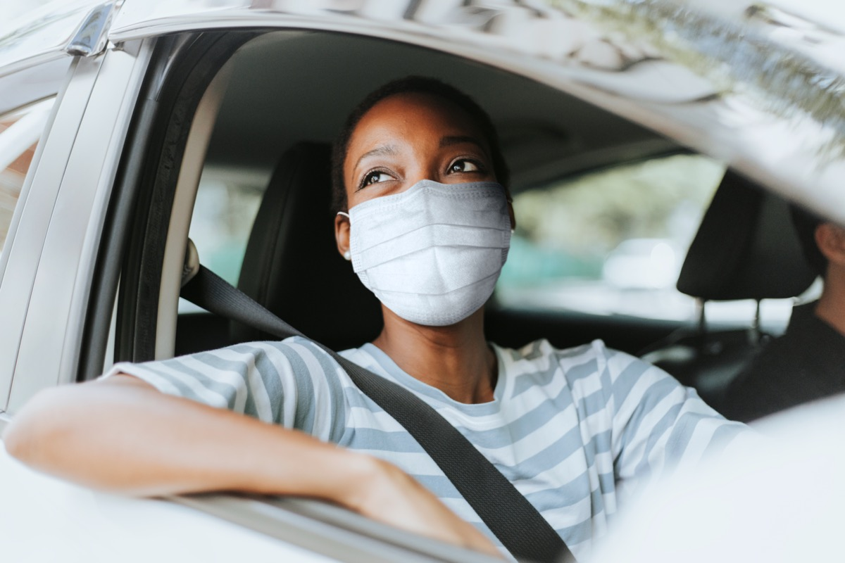 young woman wearing mask in car with window rolled down