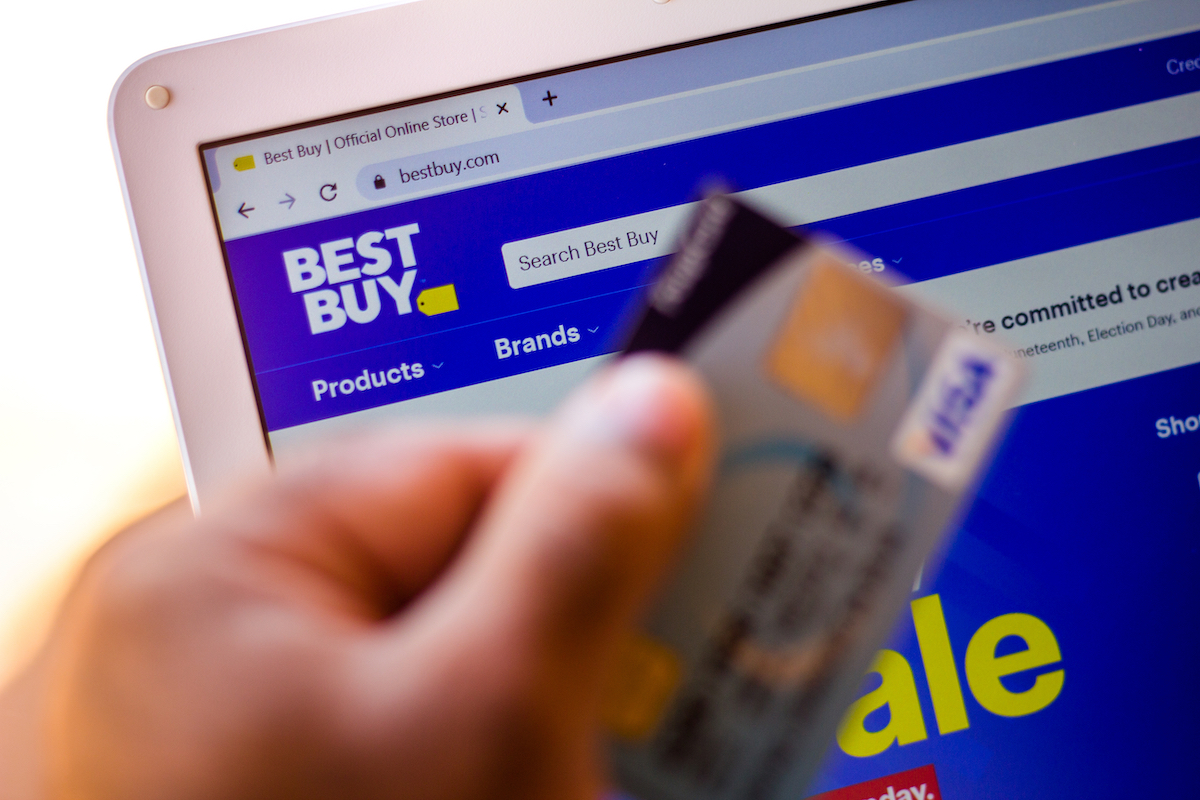 Best Buy website and hand holding a credit card