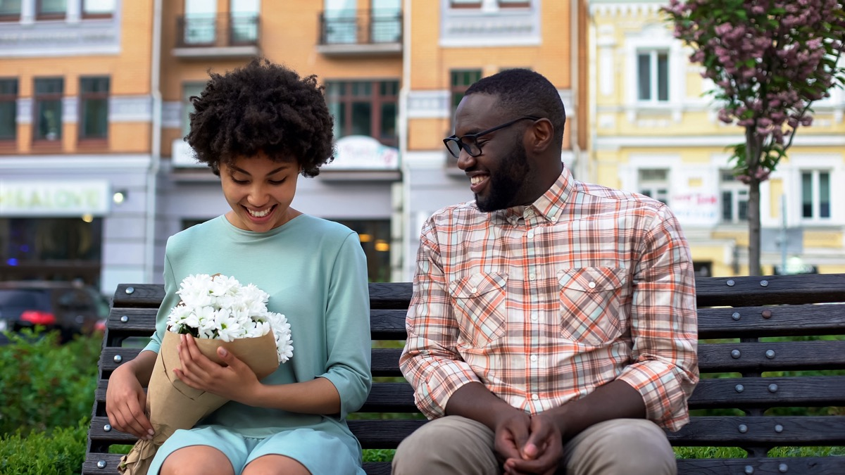 Woman holding flowers and man sitting on bench
