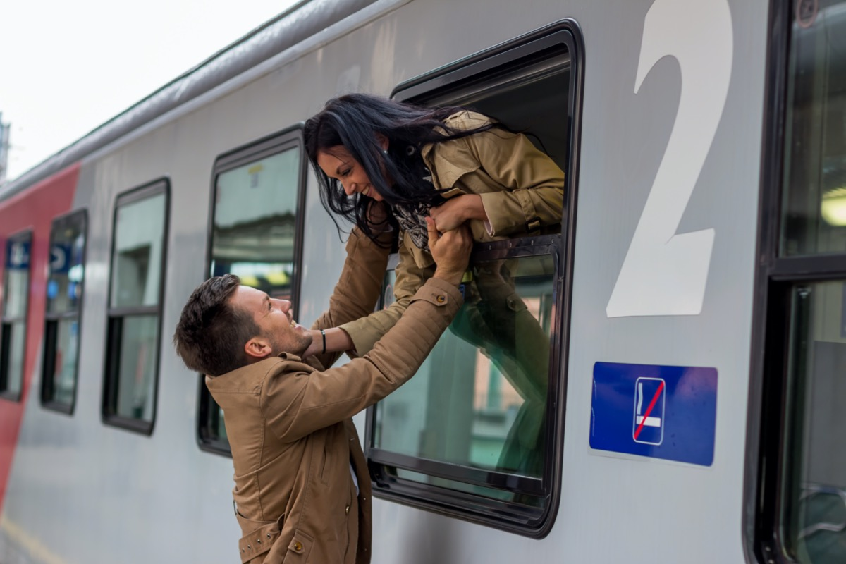 Man and woman saying goodbye through train window