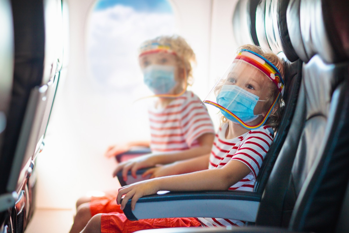 Children wearing masks and face shields on airplane