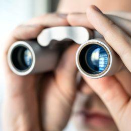 Jealous spouse using binoculars