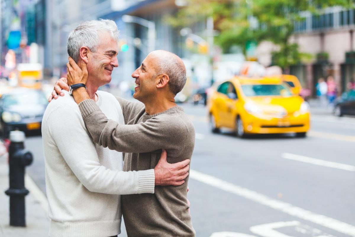 Two senior men hugging on city street