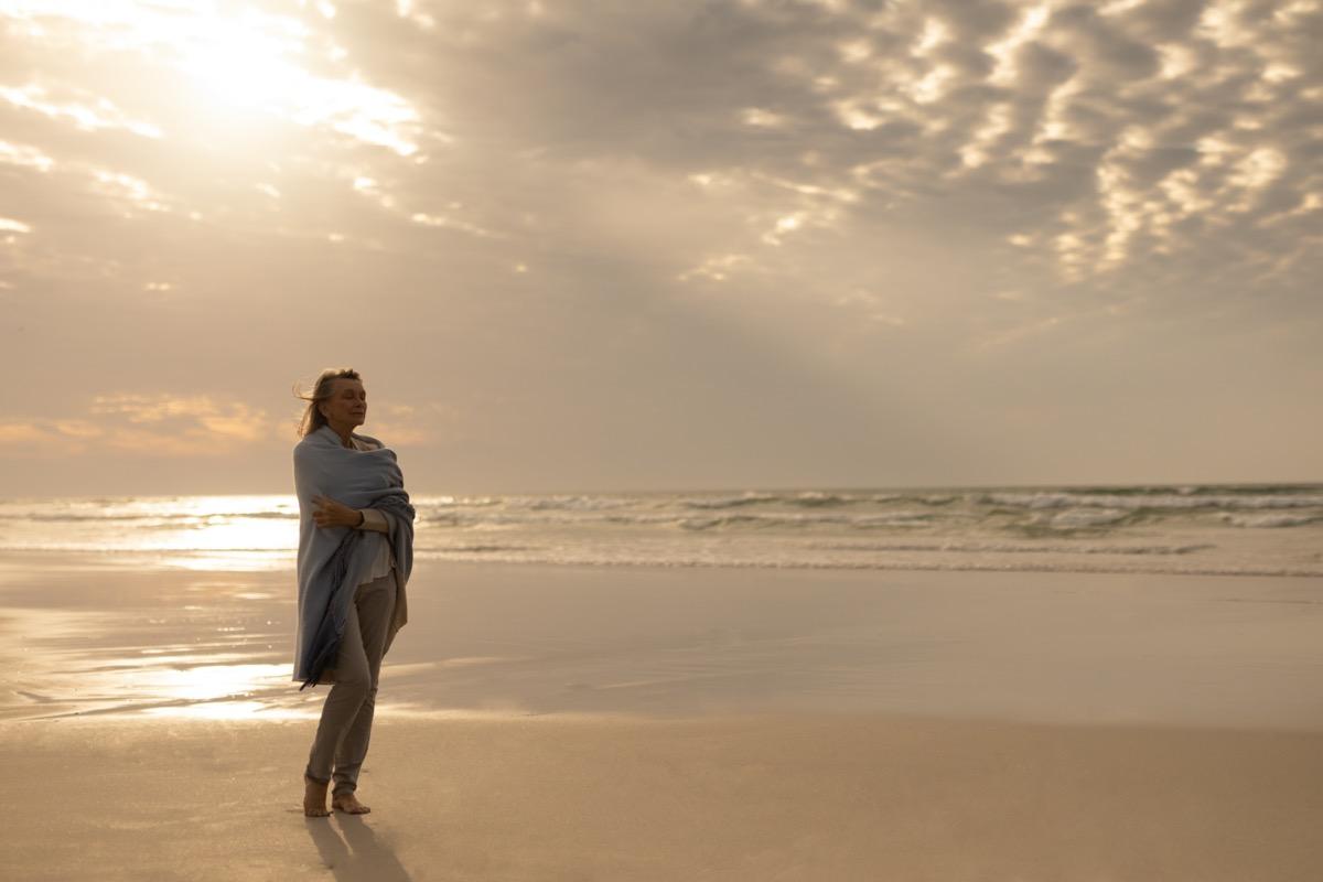 Senior woman standing alone on beach