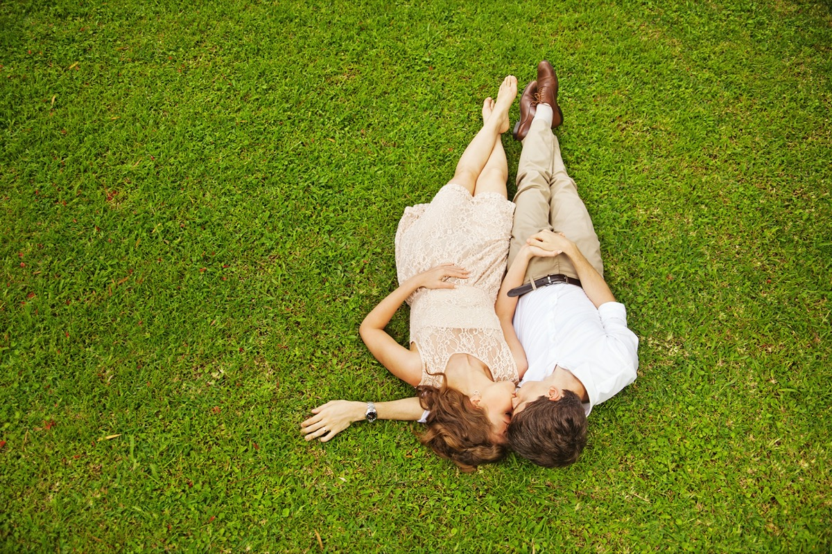 Young man and woman cuddling in grass