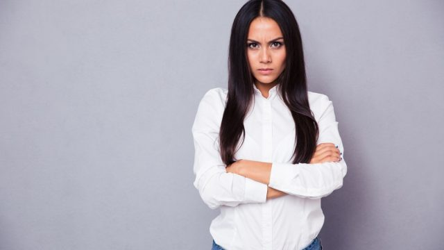 woman in a white blouse with her arms cross and an angry look on her face