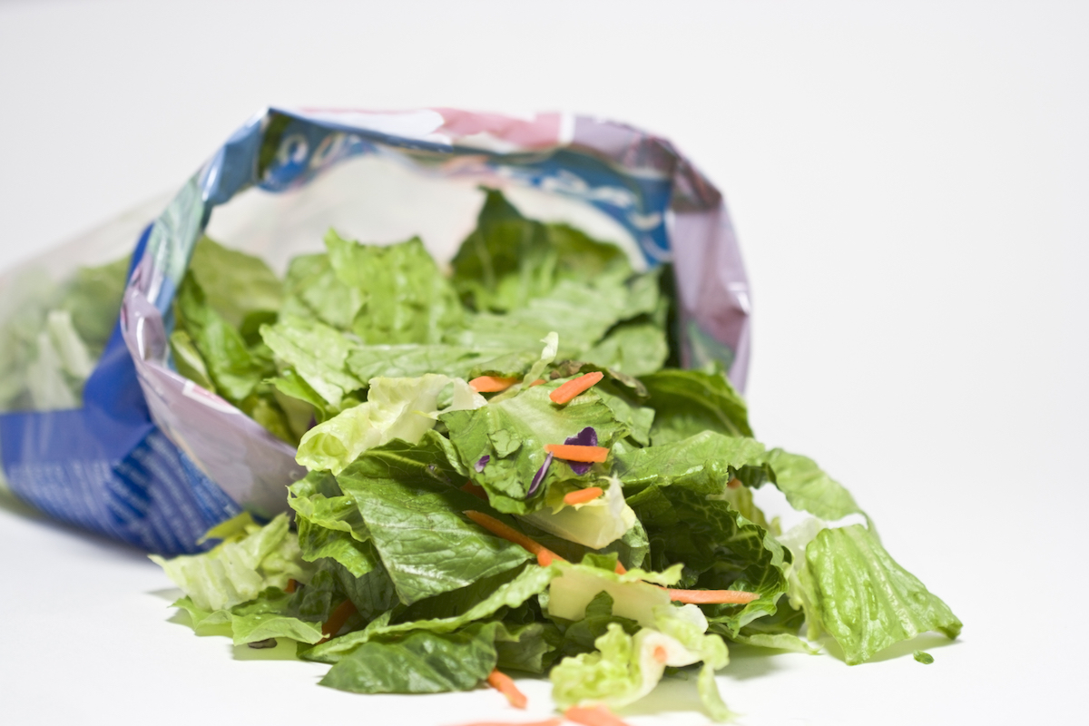 Open bag of salad on white background