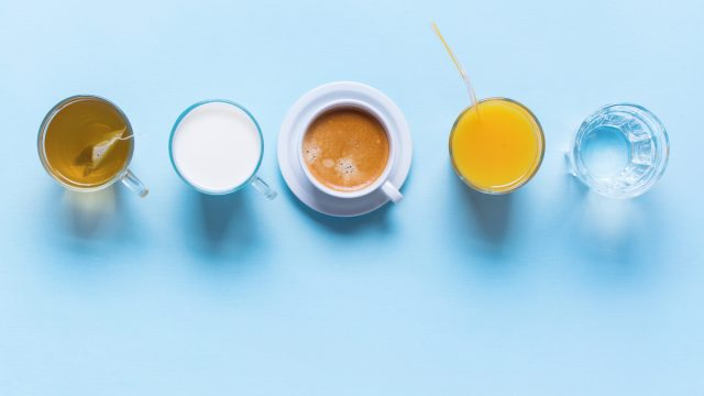 Tea, Milk, Coffee, Orange Juice, and Water on Table with Top View on Blue Background