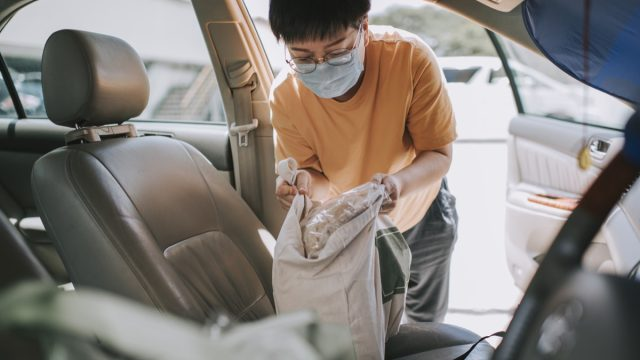 a woman removing reusable bags from her car which she just bought all groceries from supermarket with her face mask