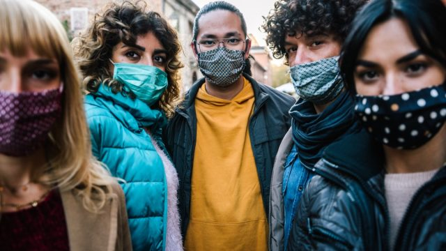 crowd of citizens in city street covered by face mask looking at camera - New normal lifestyle concept with people worried about pandemic virus - Focus on guy in the middle