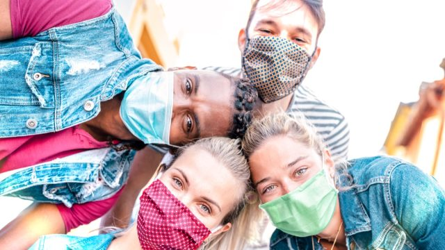 Millenial friends taking selfie smiling behind face masks – Happy friendship and new normal concept with young people having fun together – Bright sunshine filter with focus on left girl