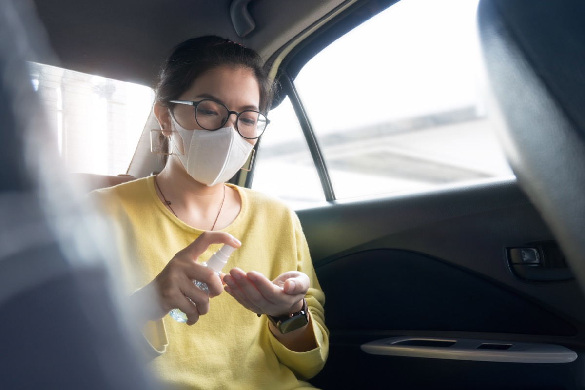 Female Passenger in green or yellow shirt and protective mask spraying disinfectant alcohol on her palms and her hands for prevent coronavirus or Coronavirus while her in a car. Cleaning, Antiseptic, Hygiene, Healthy and Health care concept.
