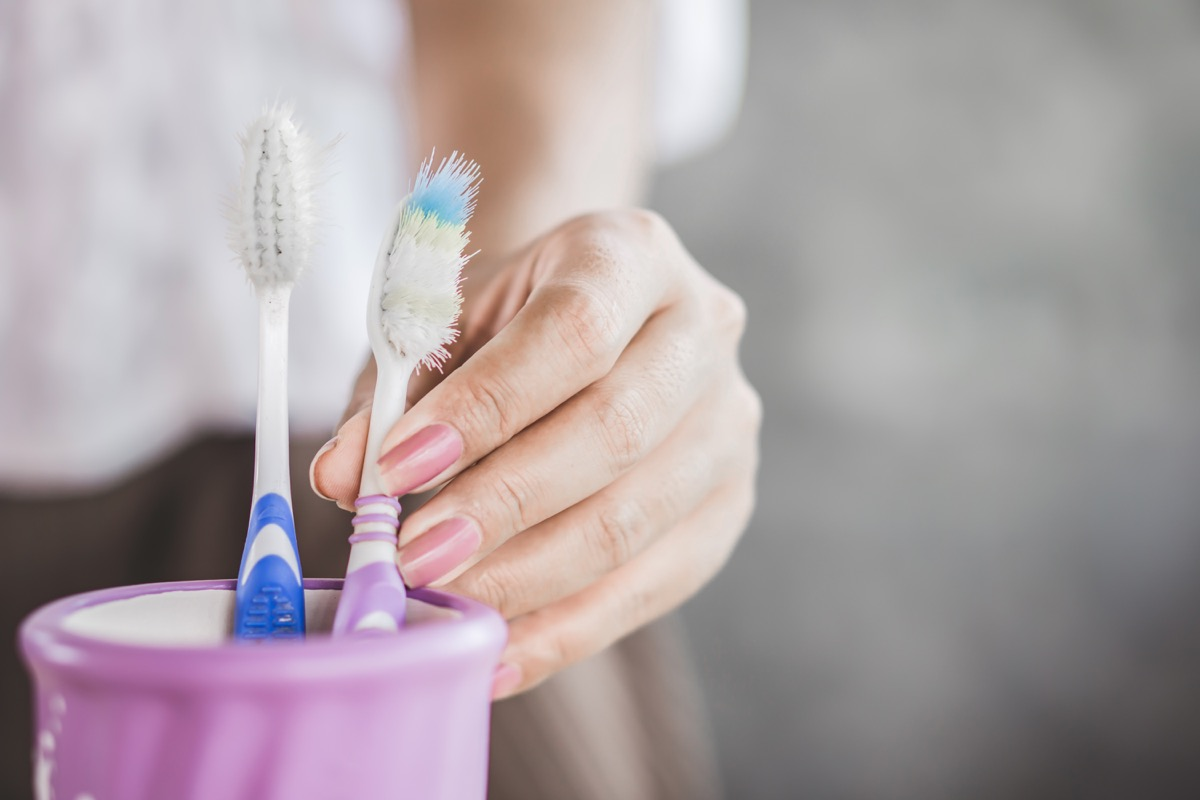 woman hand using old and destroy toothbrush closeup