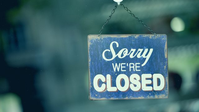 """Close-up on a blue closed sign in the window of a shop displaying the message """"Sorry we are closed"""""""