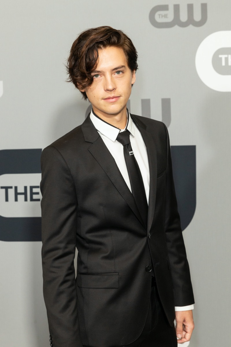 cole sprouse in black suit on red carpet in front of CW step-and-repeat