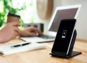 black contact phone charger on wooden desk next to person working on laptop