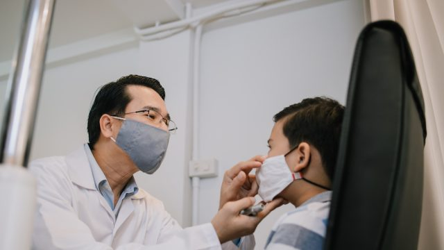 Ophthalmologist checking patient's eye while Covid spreads