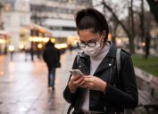Side view of young woman with face protective mask in a city at dusk, she is using smartphone.