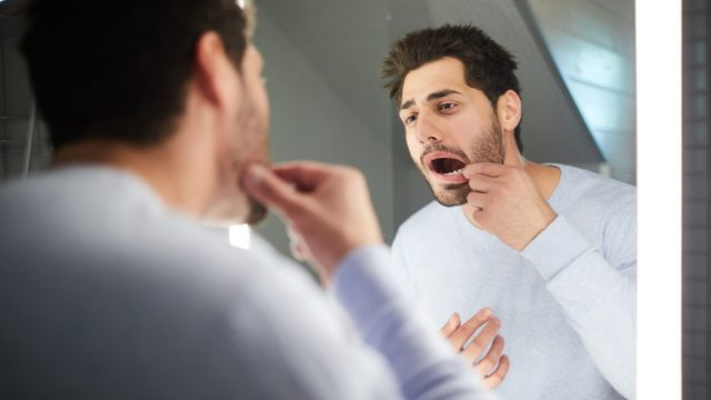 Handsome young man with stubble keeping mouth open while checking tooth and looking into mirror in bathroom