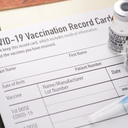 Vials of COVID-19 vaccine and a syringe sit on top of a vaccination date record card.