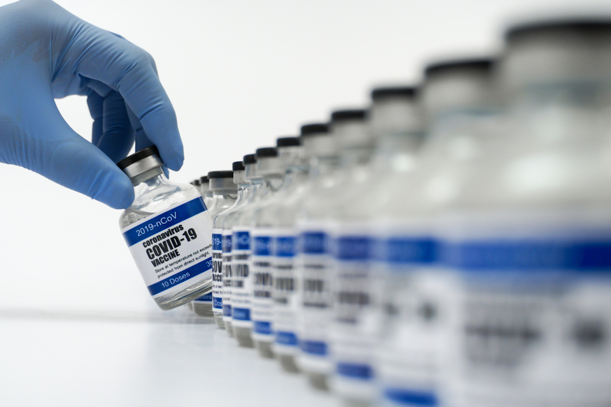 Covid-19 vaccine vial picked up by blue nitrile surgical glove-covered hand