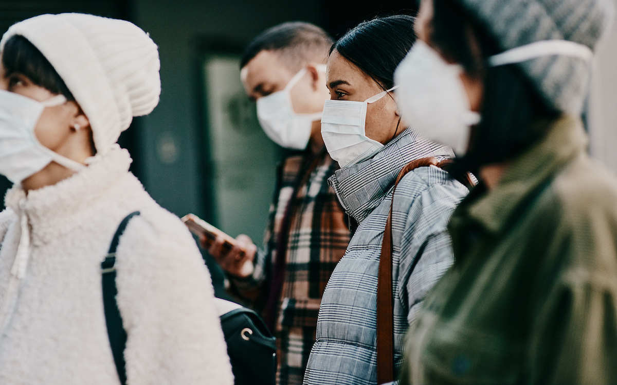 Shot of a group of young people wearing masks on the street in the cold weather
