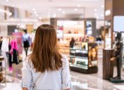 Young woman walking in department store at the mall, photographed from behind