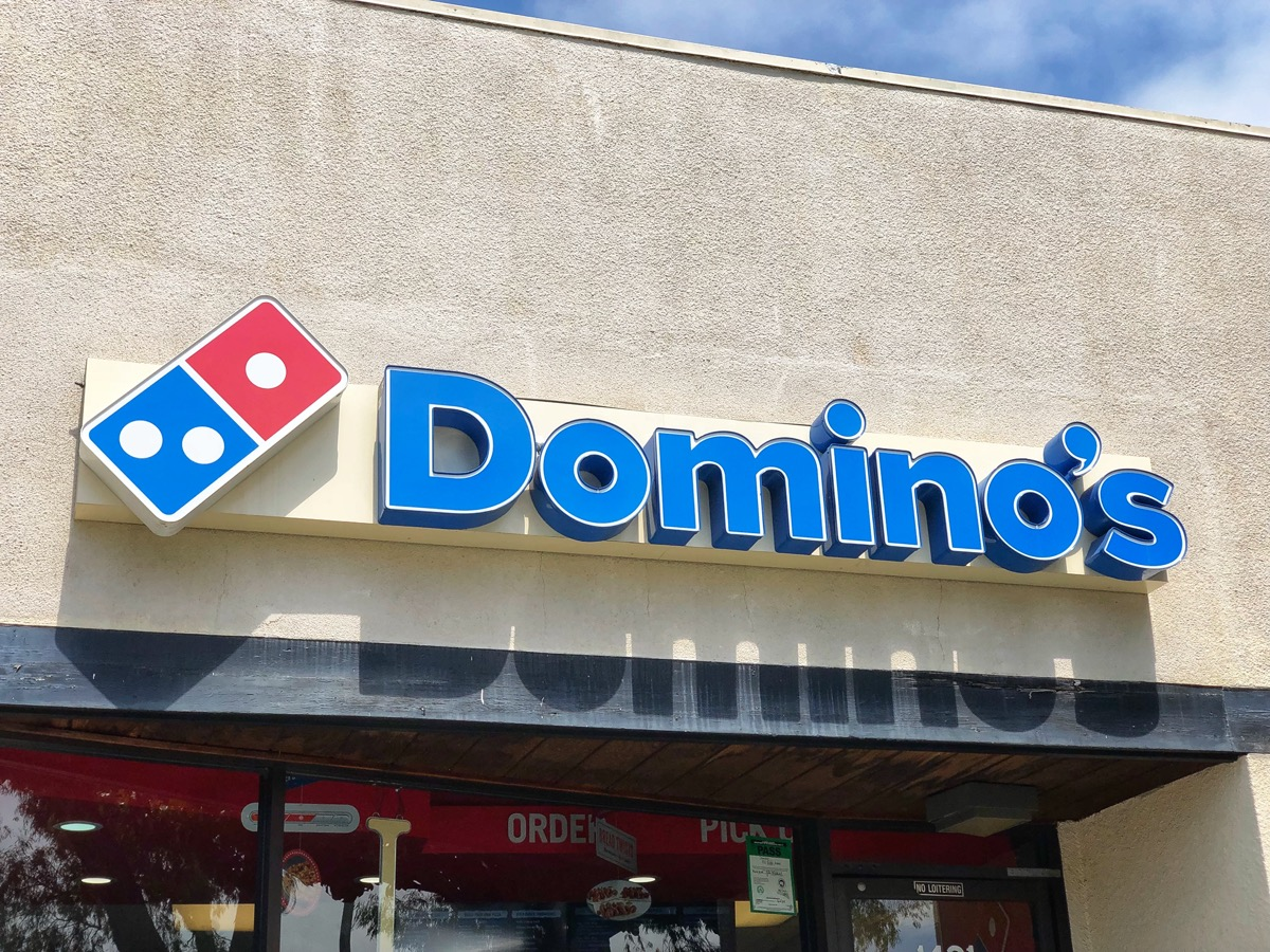 The front of a Domino's restaurant and franchise sign in Berkeley, California