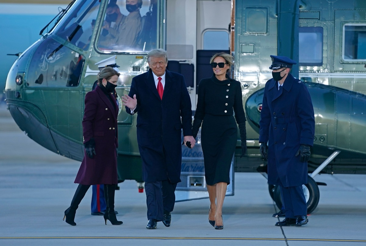 donald and melania trump walk past military members after disembarking marine one