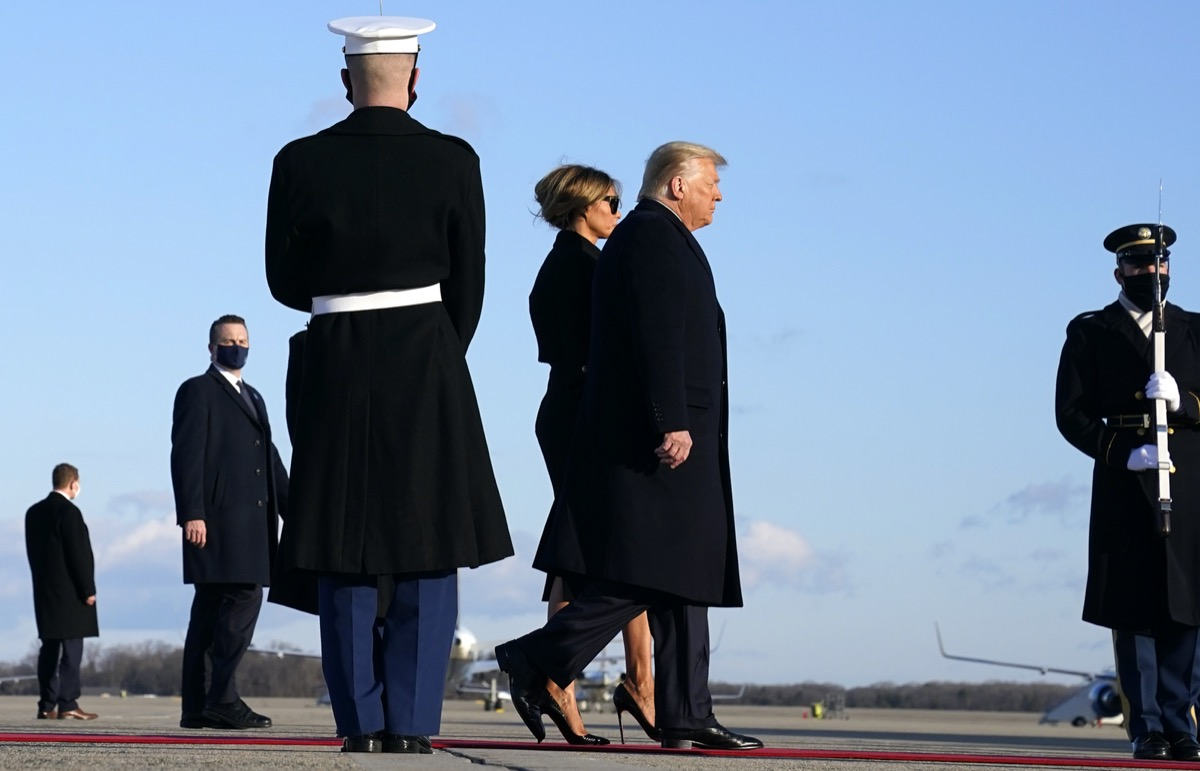 donald and melania trump walk past armed service members on the way to air force one