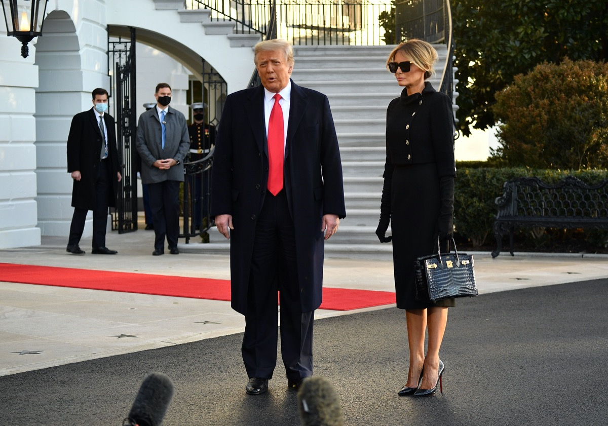 donald and melania trump stand outside white house