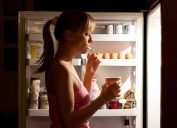 Young woman eating ice cream near refrigerator at night