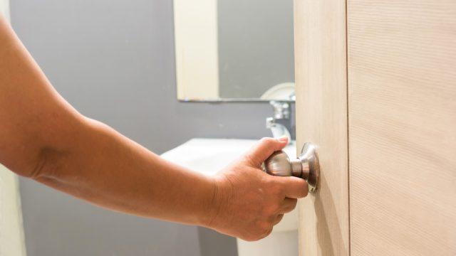 Hand opens the door to the bathroom