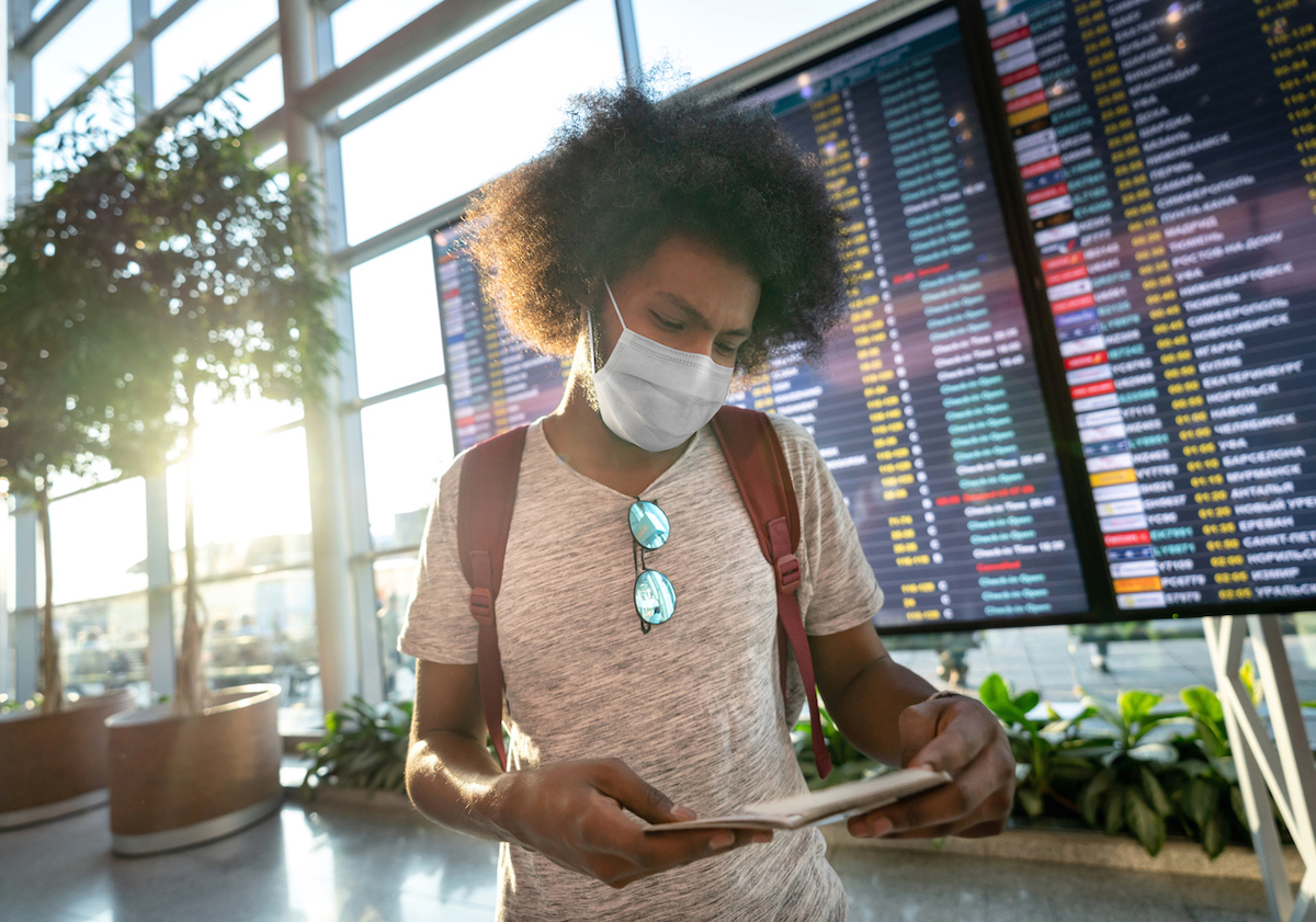 Portrait of a male traveler wearing a face mask at the airport with the flight schedule at the background while looking at his boarding pass - travel concepts