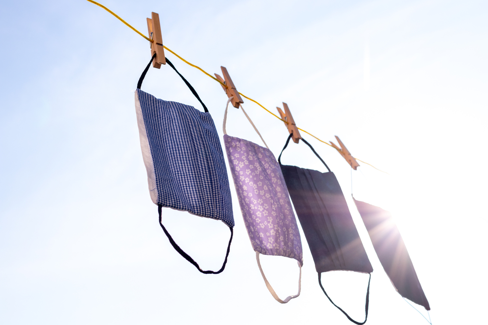 Four cloth face masks hanging in bright sunlight on a clothesline