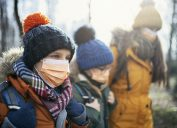 Three kids wearing back packs, face masks, and winter clothing walk outdoors.