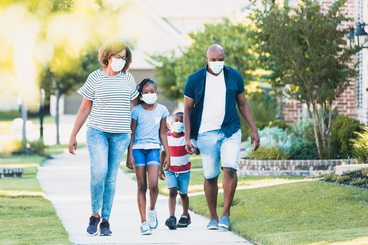 A family of four walking on a sidewalk while wearing face masks.