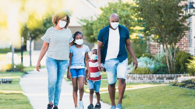A Black family of four walking on a sidewalk while wearing face masks.