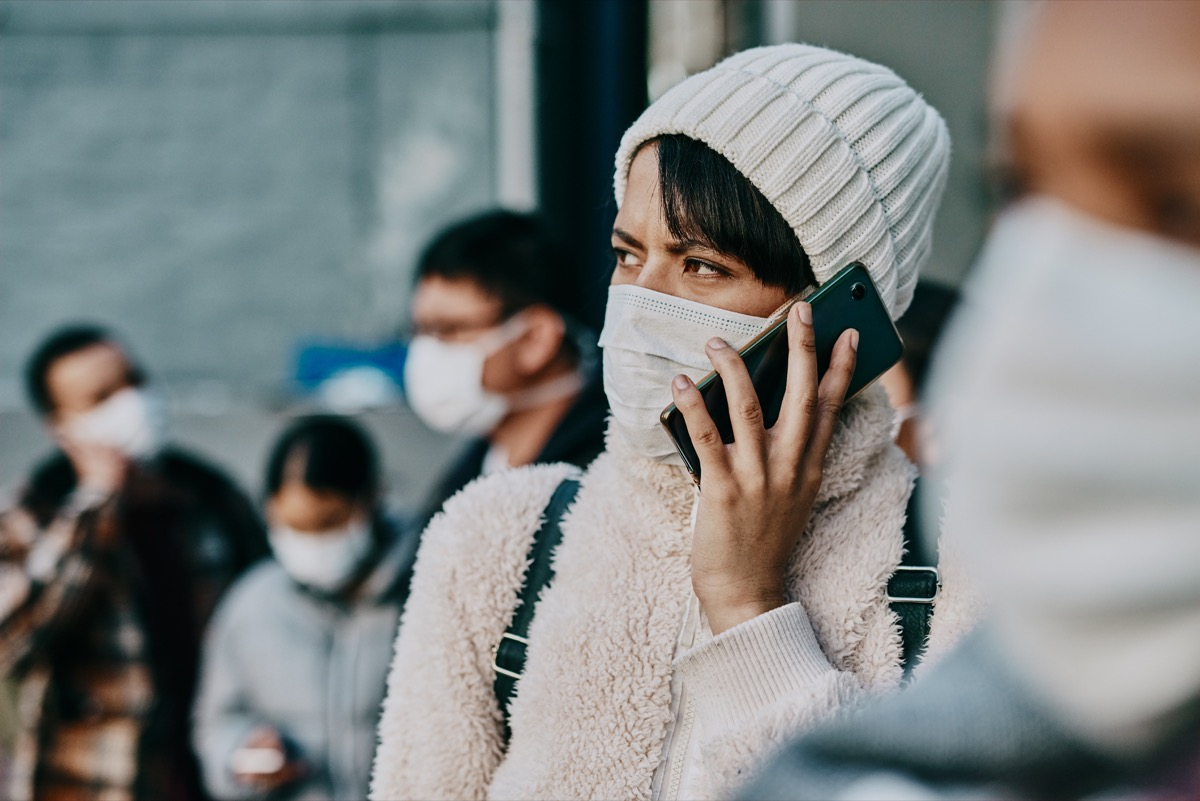 Shot of a young woman using a smartphone and wearing a mask while travelling in a foreign city