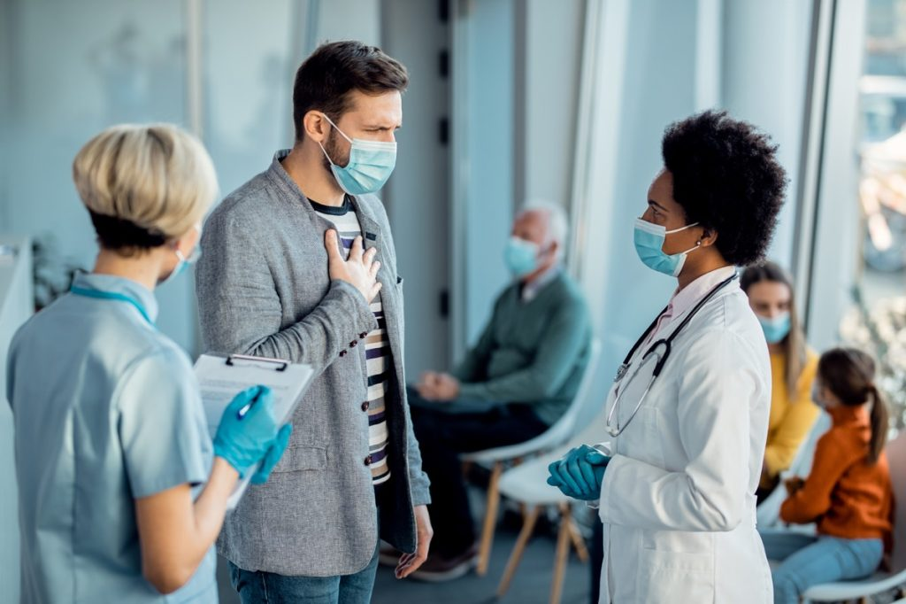 Distraught man complaining at chest pain while talking to doctor in a hallway at medical clinic during coronavirus pandemic.