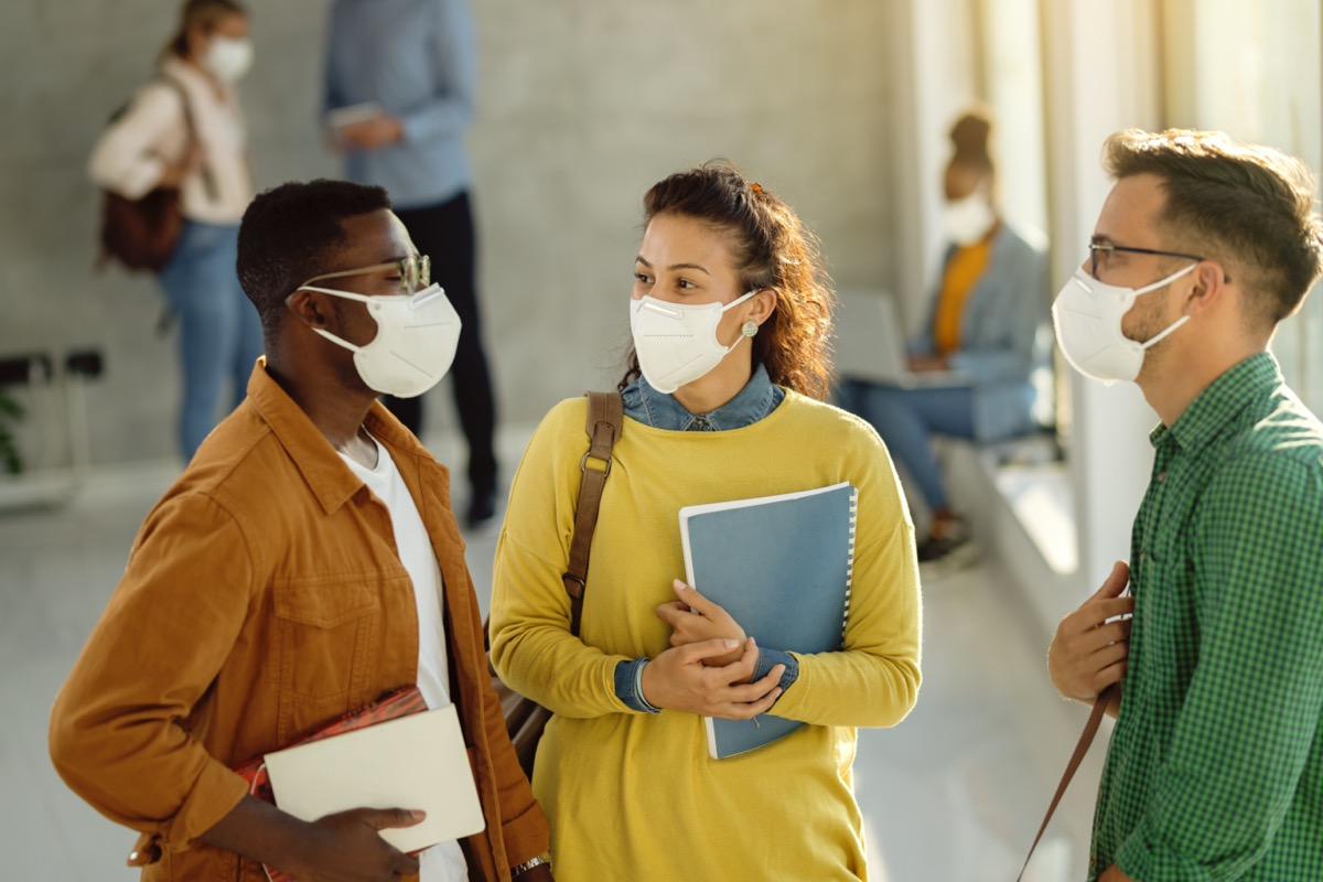 three friends in brightly colored shirts standing in school building wearing masks and holding notebooks