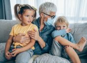 Grandmother with a protective medical facial mask plays with her grandson and granddaughter on the sofa at home during Coronavirus/COVID-19 pandemic.