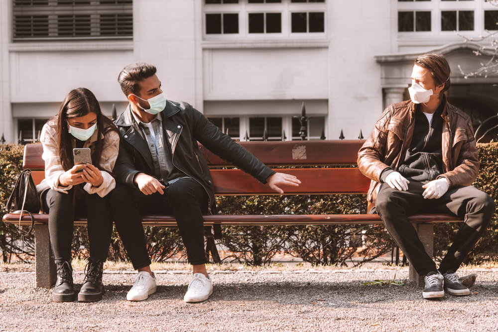 A young couple sitting on a bunch wearing face masks distances themselves from another person on the other end of the bench.