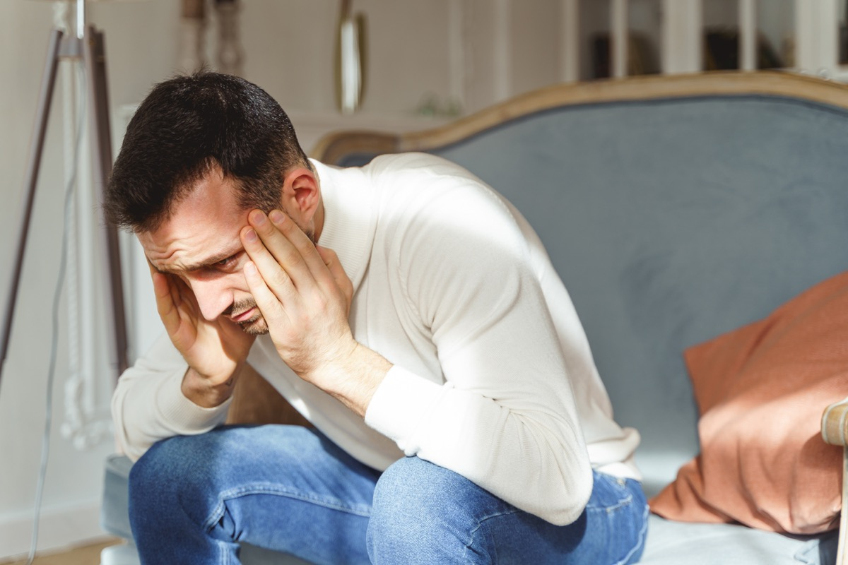 Sad male in a white pullover bending double with a pain on a sofa