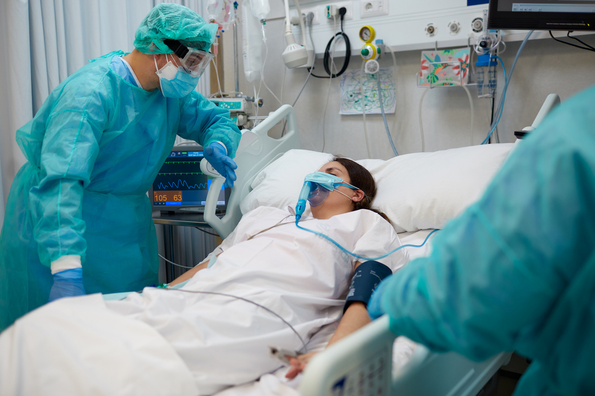 Nurse is comforting a covid patient at the ICU